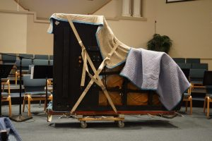 piano wrapped with moving pads and blankets