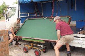 Our Movers disassemble and load the pool table into the truck easily and effortlessly. truck edit